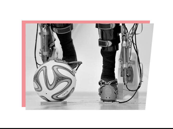 Beine im Exoskelett stoßen einen Ball